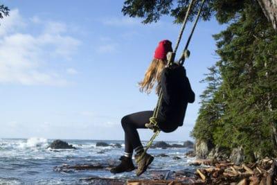 Emma swinging near ocean in tofino
